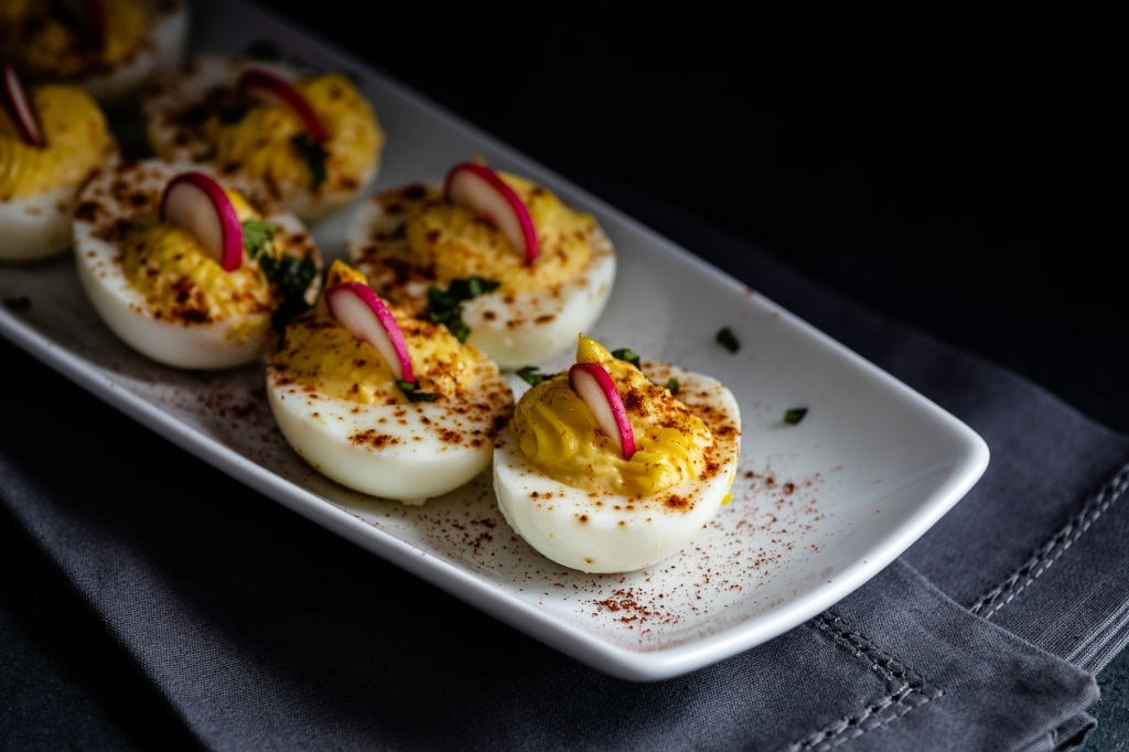 Keto deviled eggs on a white plate, garnished with paprika, radishes and chopped fresh basil