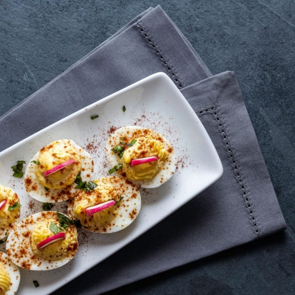 low carb deviled eggs topped with radishes, paprika and fresh basil